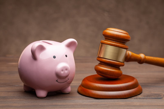 Piggy bank and judge gavel on wooden brown background