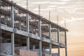 Building construction and scaffolding at sunset.