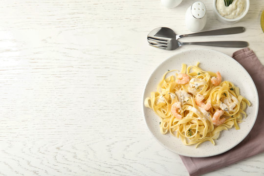 Delicious pasta with shrimps served on white wooden table, flat lay. Space for text