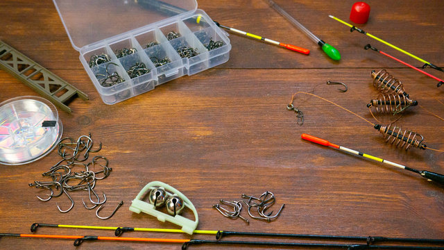 Fishing tackle on wooden brown table background. Equipment used by anglers when fishing. Hooks, lines, sinkers, floats, rods, tackle boxes
