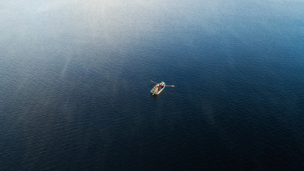 Aerial Boat on the lake. Aerial view on two fishermans in a boat on a lake, rowed to the shore. Foggy summer morning.