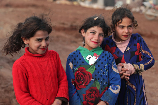 Internally displaced girls pose for a picture at a makeshift camp in Azaz