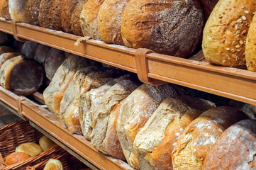 Foto auf Leinwand Brot Shelves with loaves of fresh baked bread on display in bakery