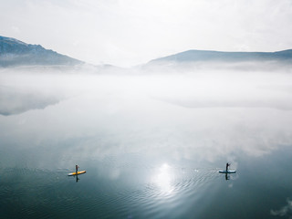 Aerial view of women stand up paddle boarding in lake