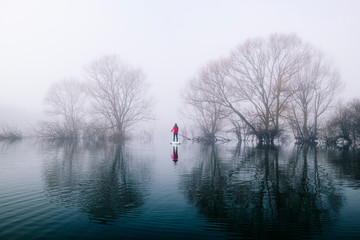Young woman stand up paddle surfing on a lake in the fog