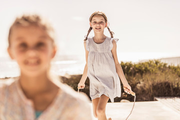 Happy girl playing with skipping rope on terrace of a beach house