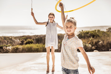 Two happy girls playing with skipping rope and hoola hoop on terrace of a beach house