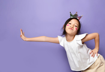 Frolic asian Korean kid girl in crown with red hearts sign on cheek is posing with her hand on something leaning pushing