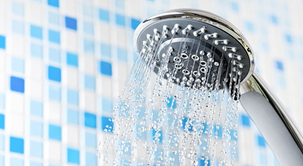 Shower head with running water in blue bathroom