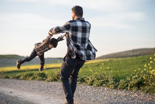 Spinning father grabbing his son with his arms