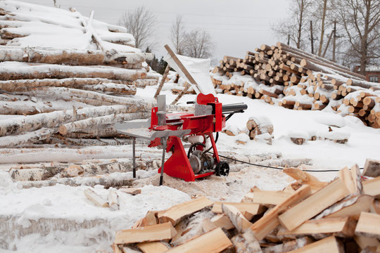 red woodcutter stands in the middle of split logs in winter next to the production