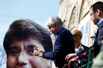 Rod Blagojevich autographs a cardboard photo of himself outside his home after U.S. President Donald Trump commuted his prison sentence, in Chicago