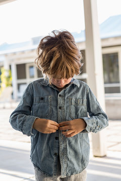 Boy buttoning up his denim shirt outdoors