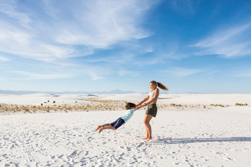 teen girl swinging her 6 year old brother in sand, White Sands Nat'l Monument, NM,White Sands National Monument