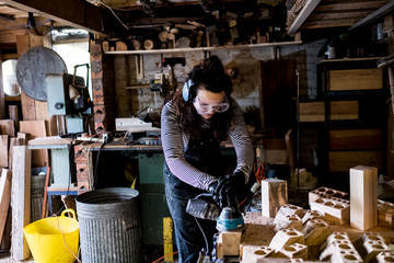 Woman with long brown hair wearing dungarees, safety glasses and ear protectors standing in wood workshop, using sander. Wall mural
