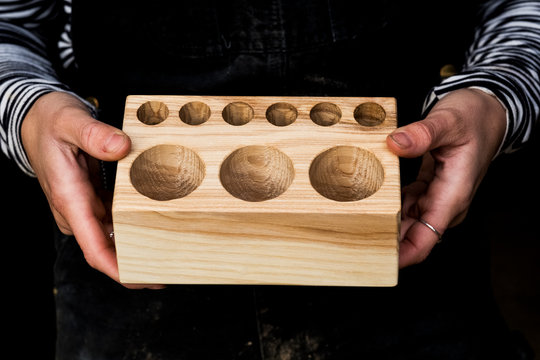 Close up of young woman holding wooden block with circular holes of different sizes