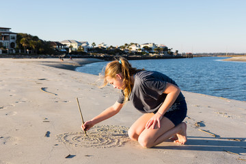A teenage girl playing in sand dunes, at the beach,St Simon's Island