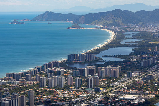 Coastal neighbourhood Barra da Tijuca in Rio de Janeiro, Brazil, seen from a high vantage point with high rise luxury buildings in the foreground, mountains and swamp land lakes in the background