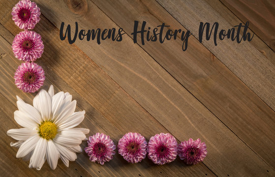 Womens History Month on wooden board with pink purple chrysanthemums flower border flat lay