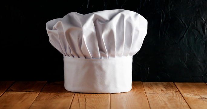 Cook hat on wooden desk and free space for your decoration.