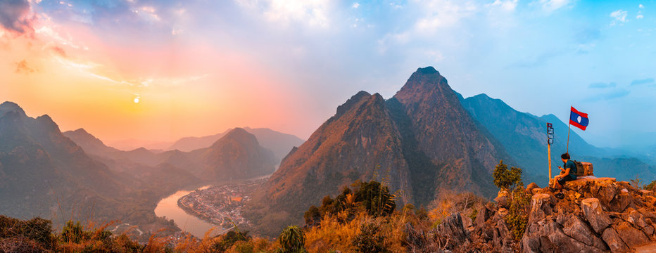 Sunset panoramic view of couple of trekkers sitting on a rock on top of Nong Khiaw View Point with beautiful mountain and Nam Ou river in background, Luang Prabang Province, Northern Laos.
