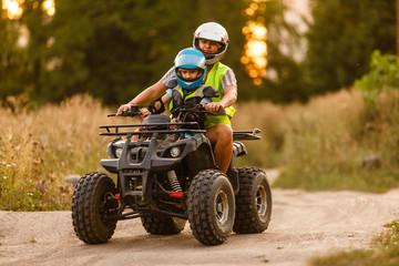 little boy with instructor on a quad bike Papier Peint