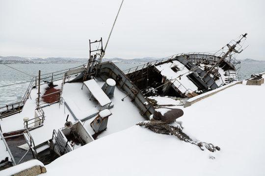 Old fishing ship in disrepair sank at pier