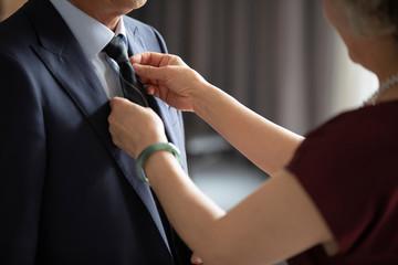 Happy senior Chinese woman tying husband's tie