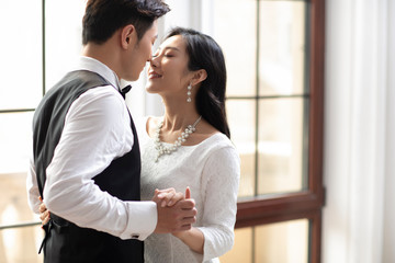Happy young Chinese couple kissing at home