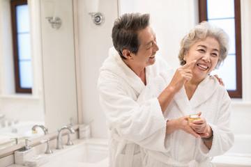 Happy senior Chinese couple applying moisturizer in bathroom