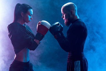Woman exercising with trainer at boxing and self defense lesson, studio, smoke on background. Aggresively look each other. Stand in front.