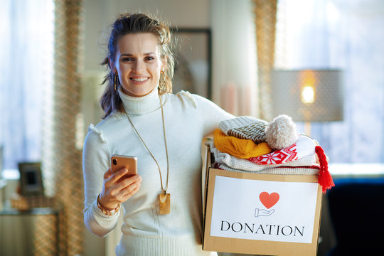 happy stylish woman with donation box with clothes using app