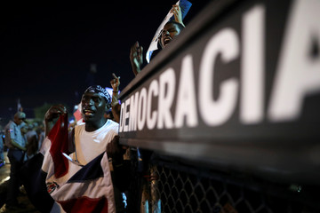 People react at a gathering in front of the Central Electoral Board to protest on the suspension of nationwide municipal elections due to an electronic glitch only four hours after voting began on last Sunday, in Santo Domingo