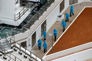 Health workers arrive at the newly-built public housing Chun Yeung Estate for quarantining passengers from the cruise ship Diamond Princess, following the outbreak of the new coronavirus, at Fo Tan in Hong Kong