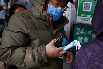 A man buys face masks at a pharmacy as the country is hit by an outbreak of the new coronavirus, in Beijing