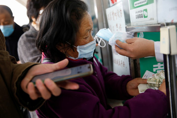 People buy face masks at a pharmacy as the country is hit by an outbreak of the new coronavirus, in Beijing