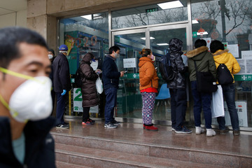 People queue outside a pharmacy to buy face masks as the country is hit by an outbreak of the new coronavirus, in Beijing