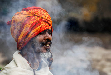 A Hindu holy man, or sadhu, reacts to the smoke as he sits at the premises of Pashupatinath Temple a day ahead of the Shivaratri festival in Kathmandu