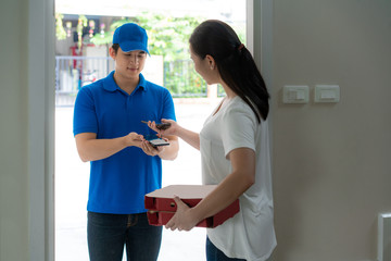 Asian delivery young man in blue uniform smile and holding pizza boxes in front house and Asian woman accepting a delivery of pizza boxes and payment QR code by smartphone from deliveryman.