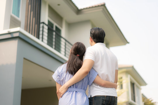Back portrait of Asian young couple standing and hugging together looking happy in front of their new house to start new life. Family, age, home, real estate and people concept..