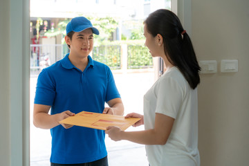 Asian delivery young man in blue uniform smile and holding letter or document envelope in front house and Asian woman accepting a delivery of envelope from deliveryman. Advertising, Transportation.