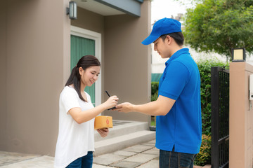 Asian delivery young man in blue uniform smile and holding smartphone in front house and Asian woman sign signature in smartphone to accepting a delivery of boxes from deliveryman..