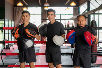 Three Asian boxer man looking at camera and pose and smile while leaned on black red ropes on boxing ring, and have a rest after hard training in black loft gym.
