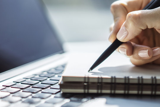 Woman writes with a pen in notebook on laptop keyboard in a sunny office, business and education concept. Close up