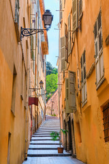 Poster Narrow alley Old traditional houses in the narrow streets in the Old Town Vielle Ville in Nice in the South of France