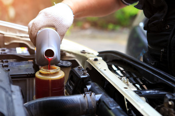 Obraz A hand filling car power steering fluid - fototapety do salonu