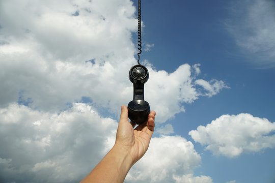 vintage black phone with line hanging from the sky. Conceptual photography talking to someone from above