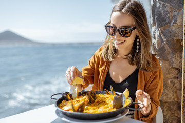 Woman eating paella, traditional spanish dish, while sitting at the restaurant terrace near the ocean. Concept of sea food and good summer vacations