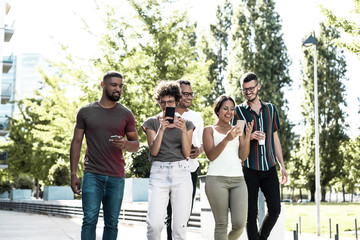 Cheerful friends using their phones for group video calls. Five people walking outside and using two smartphones, looking at screen, smiling and gesturing. Video connection concept Fotomurales