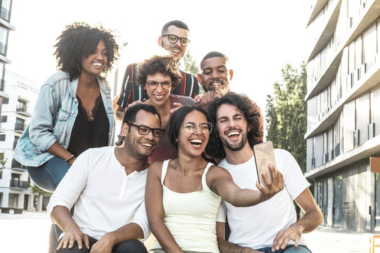 Happy excited Latin woman taking group selfie with her friends. Multiethnic team of friends posing and laughing at phone camera. Fun concept